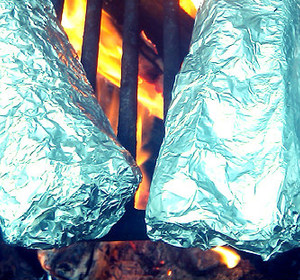 Campfire burritos in foil over camp grill