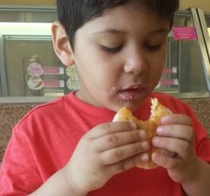 Child enjoying glazed doughnut