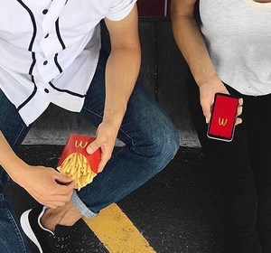 McDonald's customers enjoy food while checking out the chain's app