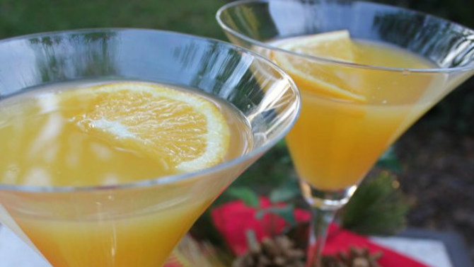 Orange creamsicle cocktails on table with oranges and pine cones