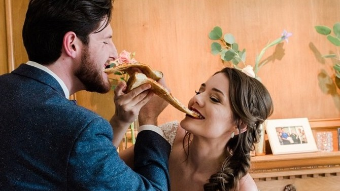 a dream couple sharing slices of pizza at their wedding reception