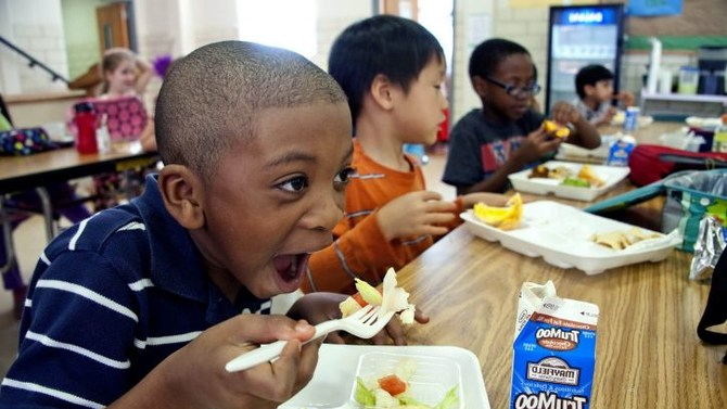 kid eating a school lunch with chocolate milk